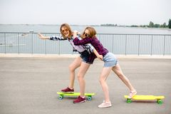 Two smiling female friends learning riding longboard with helping each other. Friendship concept royalty free stock photography