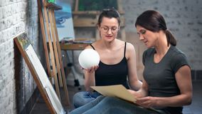 Two smiling female painter at art school studying drawing from nature holding small ball medium shot. Woman artist enjoying working at workshop drawing picture stock video