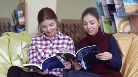 Two smiling female students having good time in library. Two smiling female students having good time while reading in library stock footage