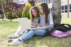 Two smiling female students are sitting on the grass. Stock Image