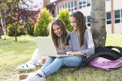 Two smiling female students are sitting on the grass. Stock Images