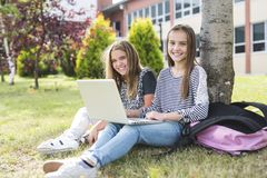 Two smiling female students are sitting on the grass. Royalty Free Stock Images