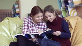 Two smiling female students thumbing through funny magazines stock footage