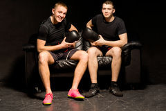 Two smiling friendly boxers sitting together. Two smiling friendly fit young boxers sitting together on a black couch in darkness holding their gloves after a Royalty Free Stock Photo