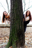 Two smiling friends behind a tree Stock Photos
