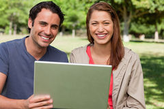 Two smiling friends looking ahead as they hold a tablet Royalty Free Stock Photos
