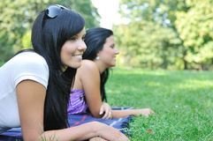 Two smiling friends lying outdoors Stock Image