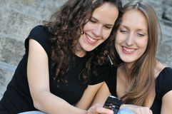 Two smiling friends with mobile phone Stock Photo