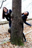 Two smiling friends peeking out from behind a tree Stock Photo