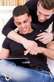 Two smiling friends pointing fingers at laptop Stock Photos