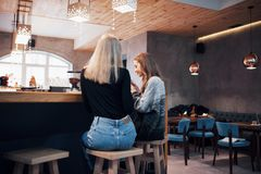 Two smiling friends reading funny online chat on modern telephone sitting with tasty coffee in restaurant.Hipster girls. Enjoying recreation time in cafe with Royalty Free Stock Image