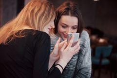 Two smiling friends reading funny online chat on modern telephone sitting with tasty coffee in restaurant.Hipster girls. Enjoying recreation time in cafe with Royalty Free Stock Photography