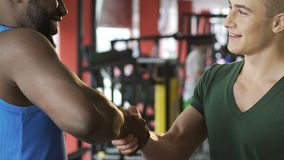 Two smiling friends saying goodbye after training in gym, friendly handshake. Stock footage stock video footage