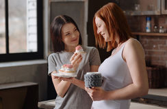 Two smiling friends trying cakes. Some sweets. Attractive red haired women holding grey cup in left hand and plate with dessert in right hand while staring at royalty free stock image