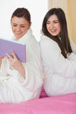 Two smiling friends wearing bathrobes sitting back to back looki Royalty Free Stock Images