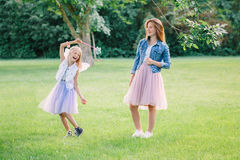 Two smiling funny Caucasian girls sisters wearing pink tutu tulle skirts in park forest meadow at sunset. Friends having fun Stock Photos