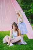 Two smiling funny Caucasian girls sisters wearing pink tutu tulle skirts in park forest meadow at sunset. Friends having fun Stock Photo