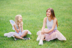Two smiling funny Caucasian girls sisters wearing pink tutu tulle skirts in park forest meadow at sunset. Friends having fun Stock Photography