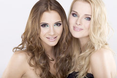 Two smiling girl friends - blond and brunette Royalty Free Stock Photos