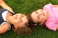 Two smiling girl lying on the grass Stock Image