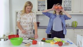 Two smiling girlfriends cokking fresh salad together and have fun at the kitchen. Two young girlfriends spend their leisure time together and cooking a fresh stock video