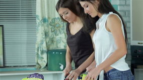 Two smiling girlfriends sliced vegetables smiling. Directly at the camera and show OK. Young smiling friends cook dinner in kitchen while cut vegetables. Food stock video footage