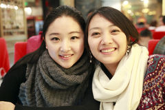 Two smiling girls. Two Asian smiling girls in a restaurant Royalty Free Stock Photography