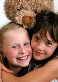 Two smiling girls. With teddy Royalty Free Stock Images