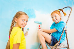 Two smiling girls with blue wall on a background Royalty Free Stock Images