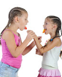 Two smiling girls with candy. royalty free stock photos