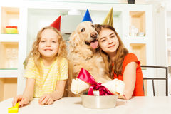 Two smiling girls celebrating pet's birthday Stock Images