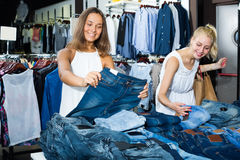Two smiling girls choosing denim trousers Royalty Free Stock Photos