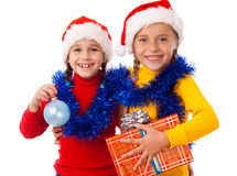 Two smiling girls with Christmas decoration. Two smiling girls in Santa hat with gift box and Christmas decoration, isolated on white Stock Image