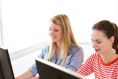 Two smiling girls in computer class. Education, technology and school concept - two smiling student girls in computer class Stock Photos