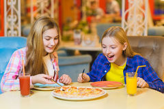 Two smiling girls eating pizza and drinking juice indoor Royalty Free Stock Photo