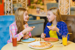 Two smiling girls eating pizza and drinking juice indoor Royalty Free Stock Image
