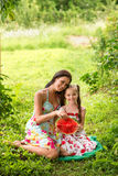 Two smiling girls eats slice of watermelon outdoors on the farm. Mother and daughter spend time together. Country style royalty free stock images
