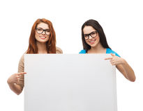 Two smiling girls with eyeglasses and blank board. Vision, health, advertisement and people concept - two smiling girls wearing eyeglasses pointing fingers to royalty free stock photos