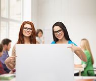 Two smiling girls with eyeglasses and blank board. Vision, health, advertisement and people concept - two smiling girls wearing eyeglasses pointing fingers to stock image