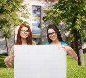 Two smiling girls with eyeglasses and blank board. Vision, health, advertisement and people concept - two smiling girls wearing eyeglasses pointing fingers to royalty free stock photography