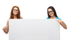 Two smiling girls with eyeglasses and blank board. Vision, health, advertisement and people concept - two smiling girls wearing eyeglasses pointing fingers to stock photos