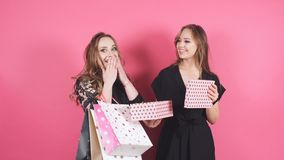 Two smiling girls give gifts to each other on an isolated background. Two smiling girls give gifts to each other on an isolated background stock video footage
