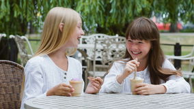 Two smiling girls or Happy children with ice cream outdoors.  stock video footage