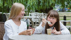 Two smiling girls or Happy children with ice cream outdoors.  stock footage