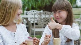 Two smiling girls or Happy children with ice cream outdoors.  stock video