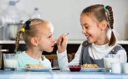 Two smiling girls having breakfast with oatmeal porridge Royalty Free Stock Image