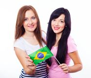 Two smiling girls holding a Brazilian flag. Royalty Free Stock Photo