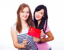Two smiling girls holding Chinese flag. Royalty Free Stock Image