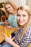 Two smiling girls holding cocktails. Having fun. Portrait of two pretty blond women holding glasses with cocktails in cafe Royalty Free Stock Photo