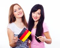 Two smiling girls holding German flag Stock Photos
